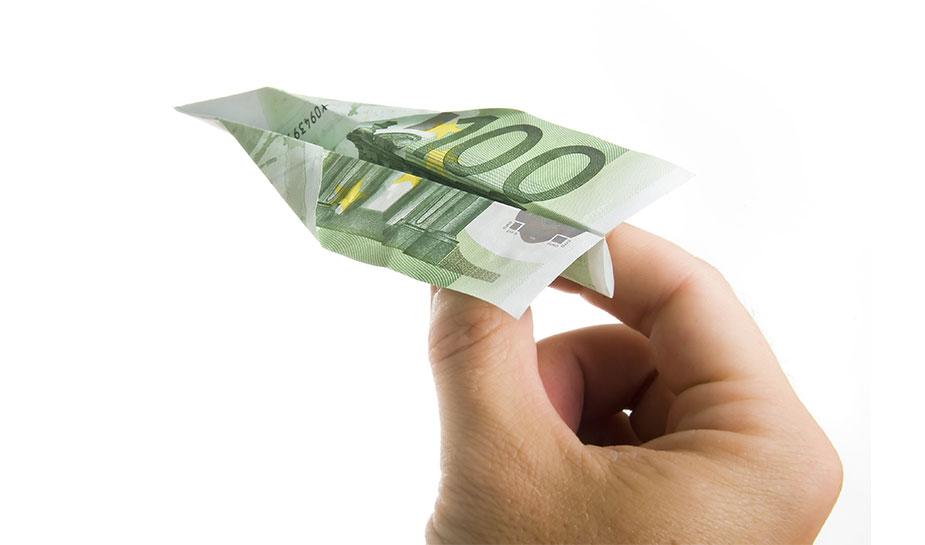 Hand die een papieren vliegtuigje gevouwen van 100 euro biljet weggooit