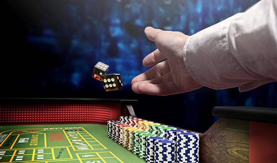 man gooit twee dobbelstenen op een groene crapstafel met casino fiches